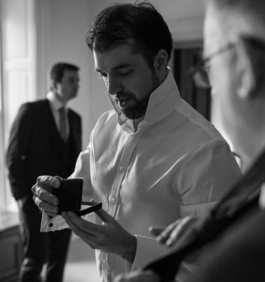 Groom looking at cufflinks in a small jewelry box