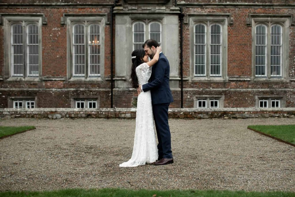 Bride and groom standing in the courtyard holding each other