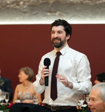 Bestman holding a mic and giving a speech