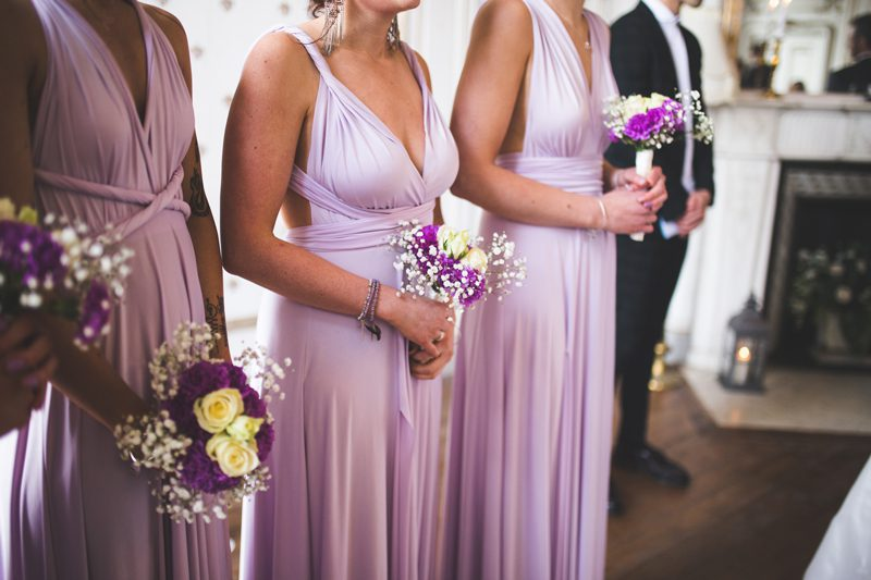 Bridesmaids in purple dresses holding bouquets