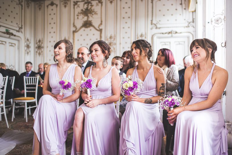 Bridesmaids sitting down in purple dresses holding bouquets