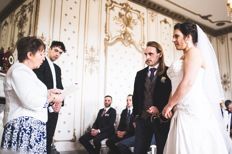 Bride and groom standing at the altar with another female reading to them