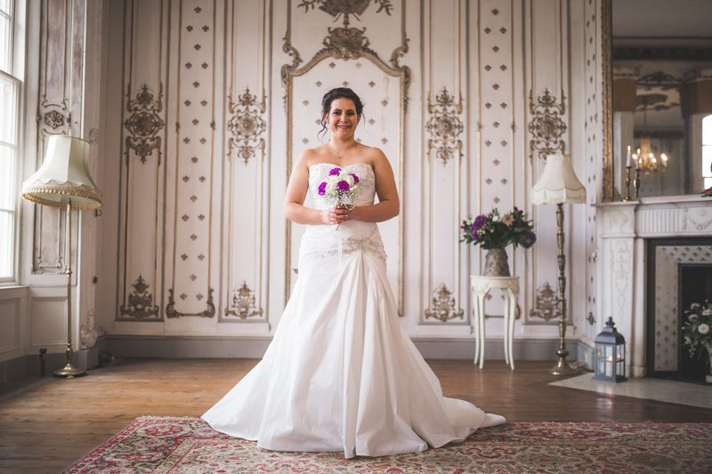 Bride in her wedding dress holding a bouquet of pink and white flowers