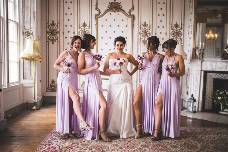 Bride in the middle of 4 bridesmaids laughing together