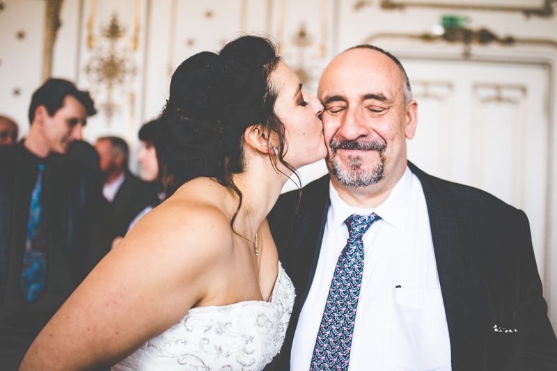 Bride kissing the father on his cheeck
