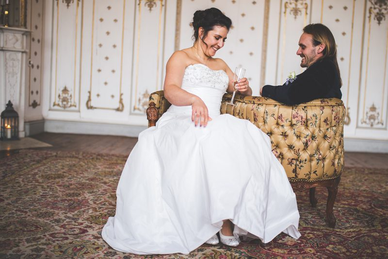 Bride and groom sitting on a couch laughing