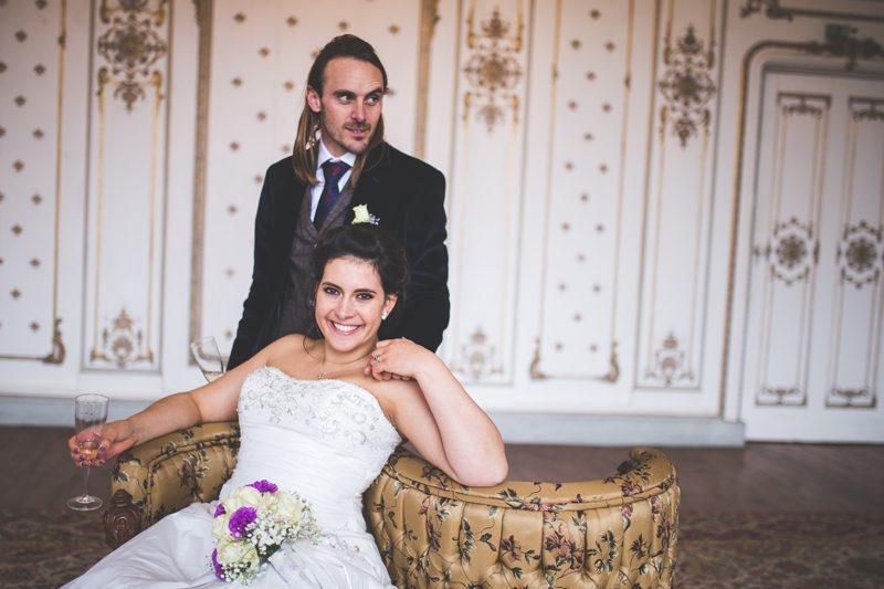 bride sitting on a couch with the groom standing behind her