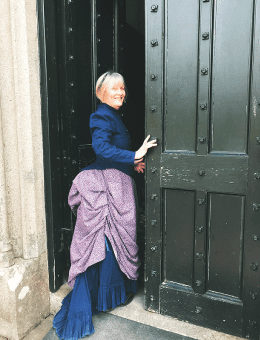 Female with blue dress smiling while walking into an open door