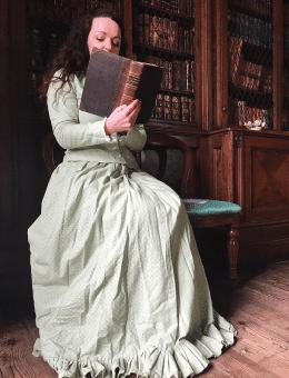 Female in a cream dress reading a book