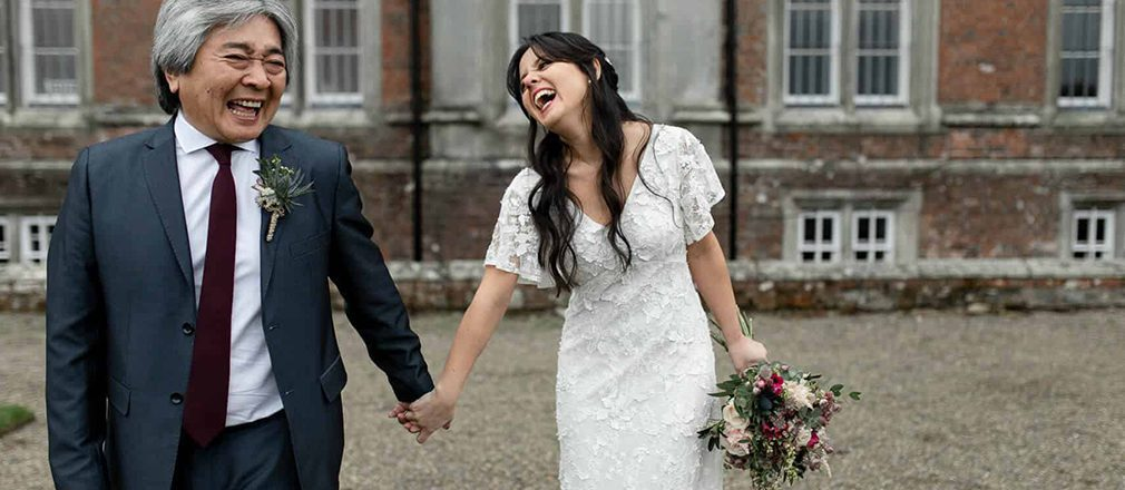 Bride and father holding hands and laughing