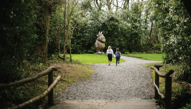 2 kids holding hands running down a gravel pathway