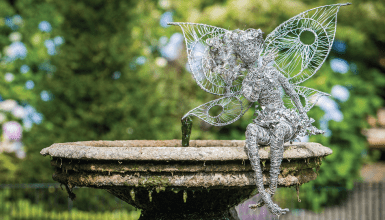 Fairy ornament sitting on a small water fountain