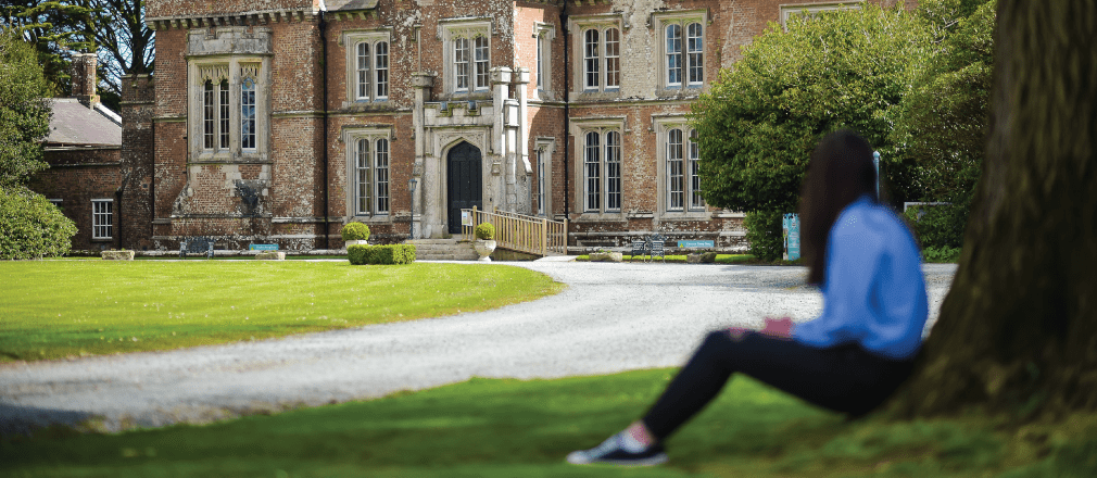 Female sitting next to a tree looking at Wells House