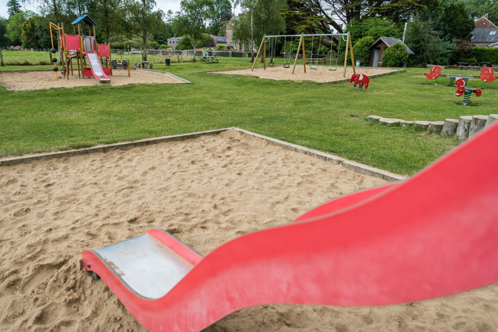 2 red slides going into sand pits and swings in a sandpit