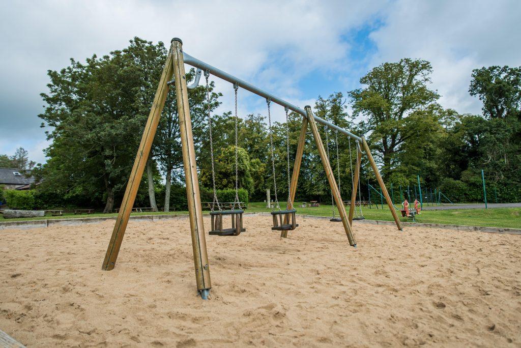 Wooden swings in a sandpit