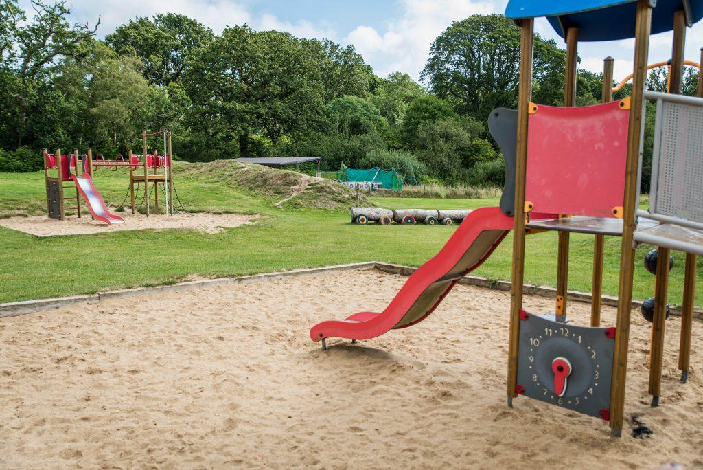 2 red sliding boards going into a huge sandpit