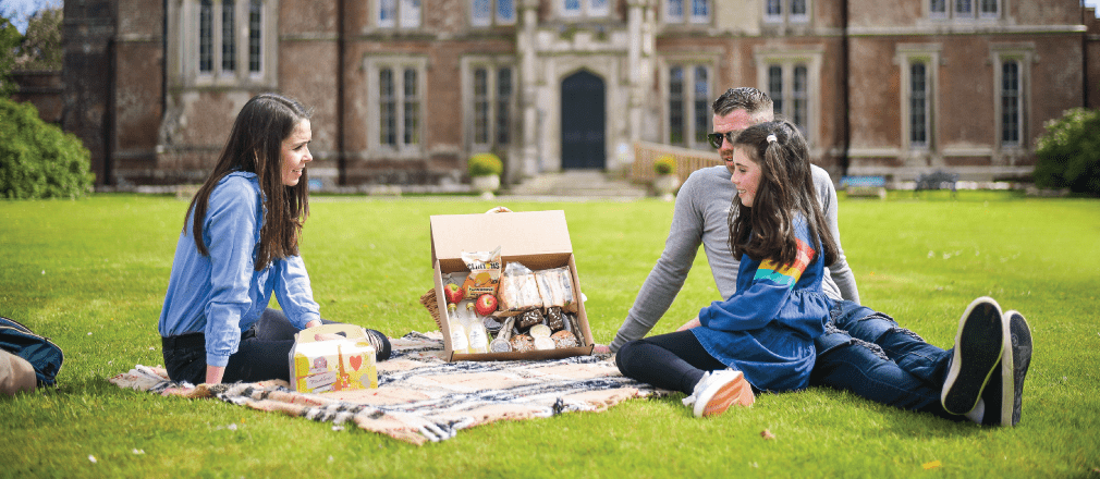 father, mother and daughter having a picnic in the garden