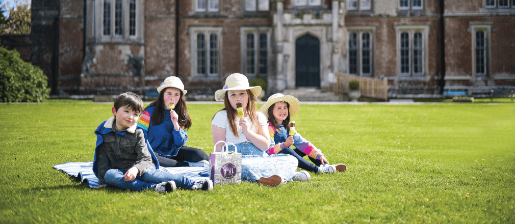 Group of kids sitting in the garden having a picnic