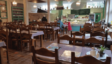 Restaurant with brown wooden tables and chairs in rows