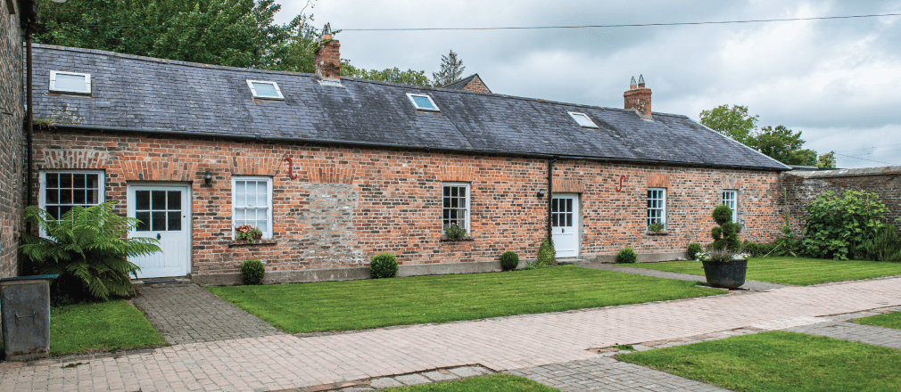 Front of the cottage with a pathway and grass on either side